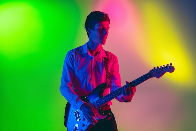 Jonge kaukasische musicus, gitarist die op gradiëntruimte speelt in neonlicht. concept van muziek, hobby, festival Gratis Foto