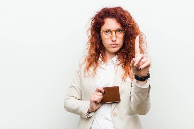 Jonge kaukasische roodharigevrouw die een portefeuille houden die nummer één met vinger tonen. Premium Foto