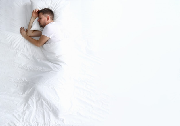 Jonge kaukasische schoonheidsvrouwenslaap op wit bed Premium Foto
