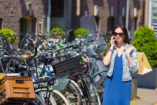 Jonge kaukasische vrouw die door celtelefoon spreekt in europese stad Premium Foto