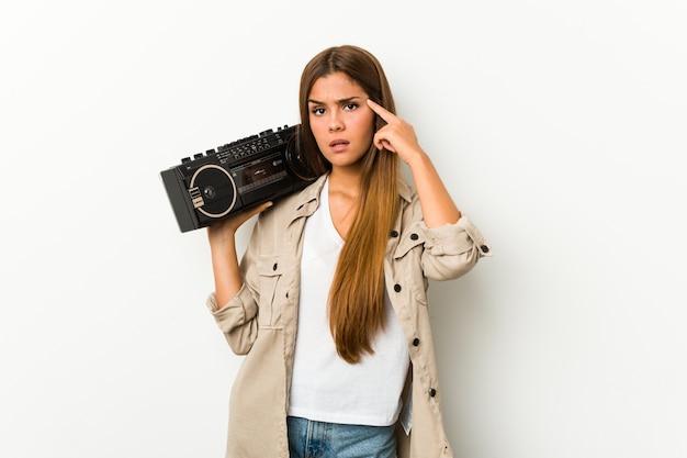 Jonge kaukasische vrouw die een guettoblaster houdt die een teleurstellinggebaar met wijsvinger toont. Premium Foto