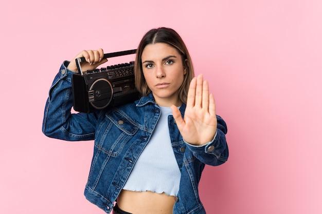 Jonge kaukasische vrouw die een guettoblaster houdt die zich met uitgestrekte hand bevindt die stopbord toont, dat u verhindert. Premium Foto