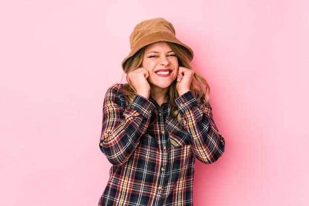 Jonge kaukasische vrouw die een hoed draagt die oren behandelt met handen. Premium Foto