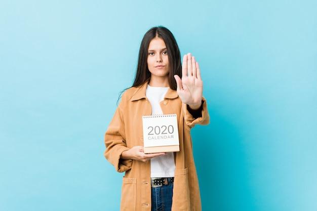 Jonge kaukasische vrouw die een kalender van de jaren 2020 houden die zich met uitgestrekte hand bevinden die eindeteken tonen, die u verhinderen. Premium Foto