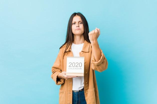Jonge kaukasische vrouw die een kalender van de jaren 2020 houdt die vuist toont aan camera, agressieve gelaatsuitdrukking. Premium Foto