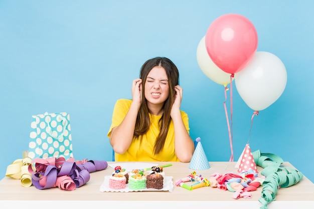 Jonge kaukasische vrouw die een verjaardag organiseert die oren behandelt met handen. Premium Foto