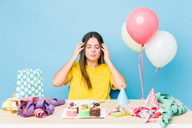 Jonge kaukasische vrouw die een verjaardag organiseert en hoofdpijn heeft. Premium Foto