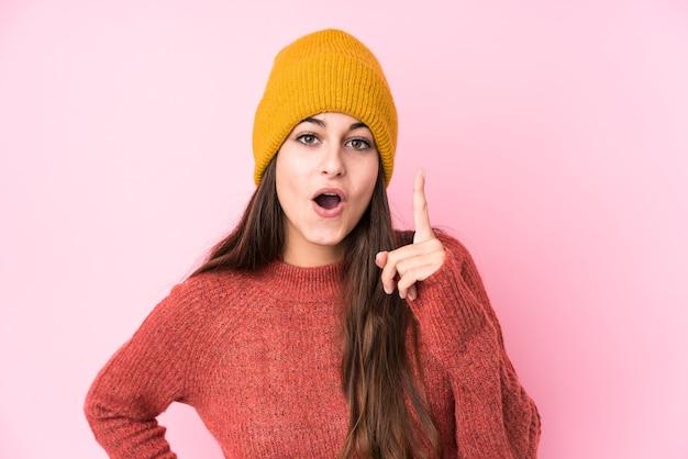 Jonge kaukasische vrouw die een wollen pet draagt die een idee, inspiratieconcept heeft. Premium Foto