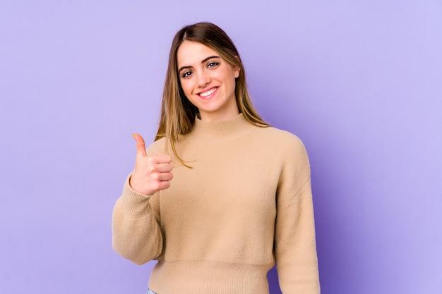 Jonge kaukasische vrouw die en duim glimlacht opheft Premium Foto