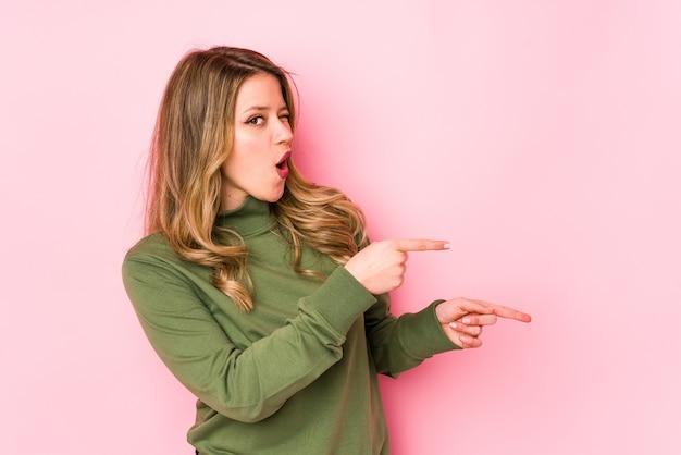 Jonge kaukasische vrouw die met wijsvingers naar een exemplaarruimte richt, opwinding en verlangen uitdrukt. Premium Foto