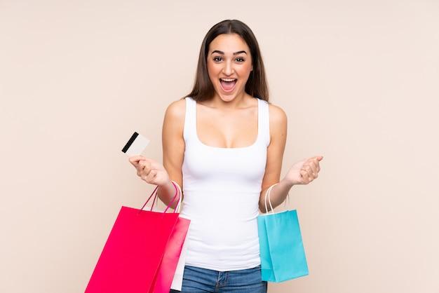 Jonge kaukasische vrouw die op beige holdings het winkelen zakken wordt geïsoleerd en verrast Premium Foto