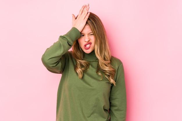 Jonge kaukasische vrouw die op roze muur wordt geïsoleerd die iets vergeet, voorhoofd met handpalm slaat en ogen sluit. Premium Foto