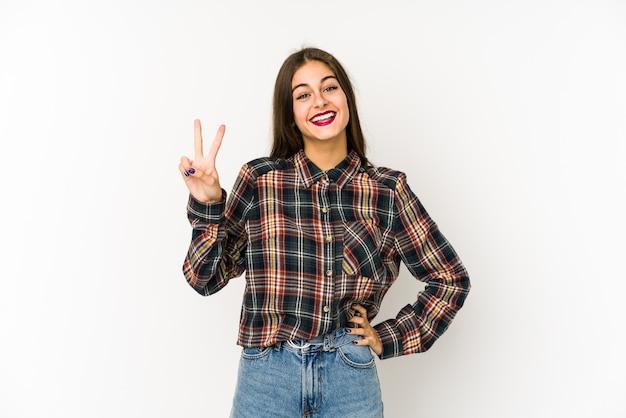 Jonge kaukasische vrouw die op witte ruimte wordt geïsoleerd die nummer twee met vingers toont. Premium Foto