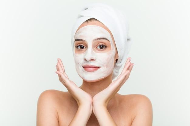 Jonge kaukasische vrouw die van offacial maskerbehandeling geniet Premium Foto