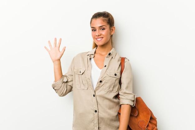 Jonge kaukasische vrouw klaar voor een reis die vrolijk tonend nummer vijf met vingers glimlacht. Premium Foto