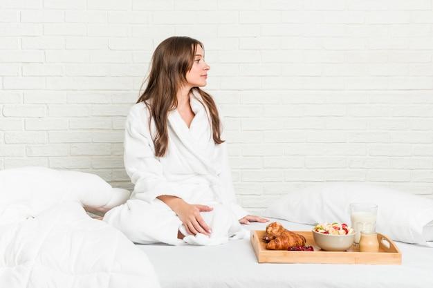 Jonge kaukasische vrouw op het bed dat links staart Premium Foto