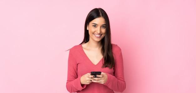 Jonge kaukasische vrouw over geïsoleerde muur die een bericht met mobiel verzendt Premium Foto