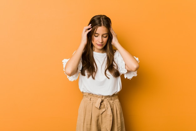 Jonge kaukasische vrouw wat betreft tempels en het hebben van hoofdpijn. Premium Foto
