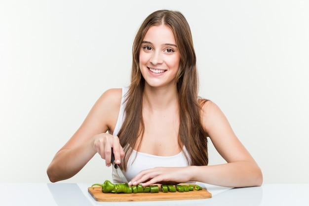 Jonge kaukasische vrouwen scherpe groenten Premium Foto