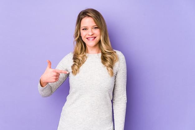 Jonge kaukasische vrouwenpersoon die met de hand naar de ruimte van een overhemdsexemplaar wijst, trots en zelfverzekerd Premium Foto