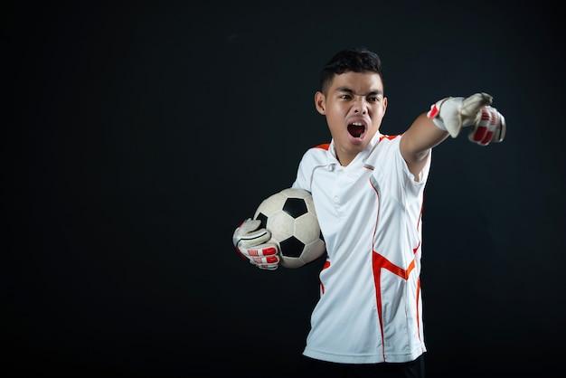 Jonge keeper voetbal man geïsoleerd van academie voetbalteam Gratis Foto