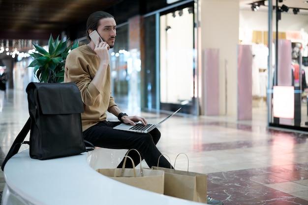 Jonge kerel belt naar een vriend om te vertellen over de verkoop in het winkelcentrum Gratis Foto
