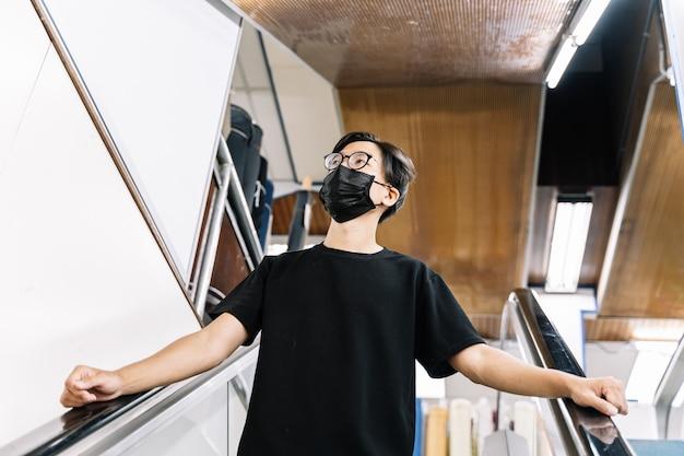 Jonge kerel die met een gezichtsmasker voor het covid-19 coronavirus winkelt Premium Foto