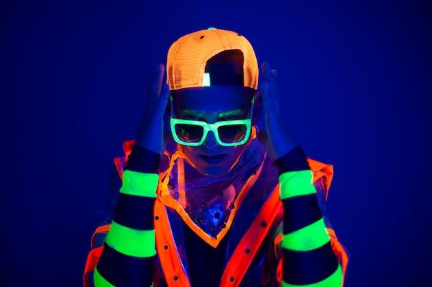 Jonge kerel in creatief kostuum met neongloed. Premium Foto