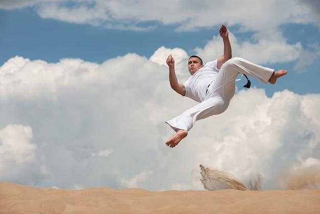 Jonge kerel leidt capoeira op hemel op backround. een man voert de schop in de sprong uit Premium Foto