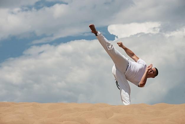 Jonge kerel leidt capoeira op hemel op backround. een man voert de schop uit Premium Foto