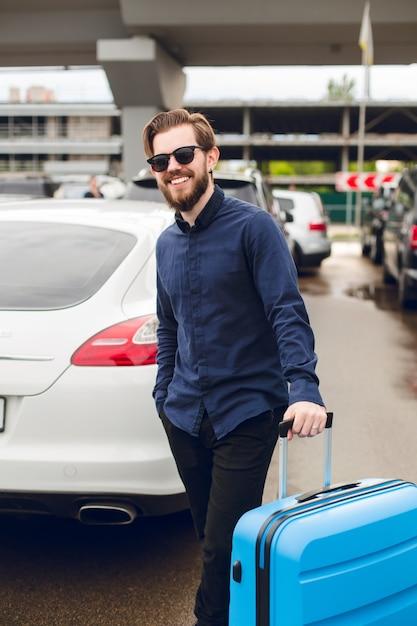 Jonge kerel met baard in zwarte zonnebril staat met koffer op parkeerterrein in luchthaven. hij draagt een zwart shirt met broek en lacht naar de camera. Gratis Foto