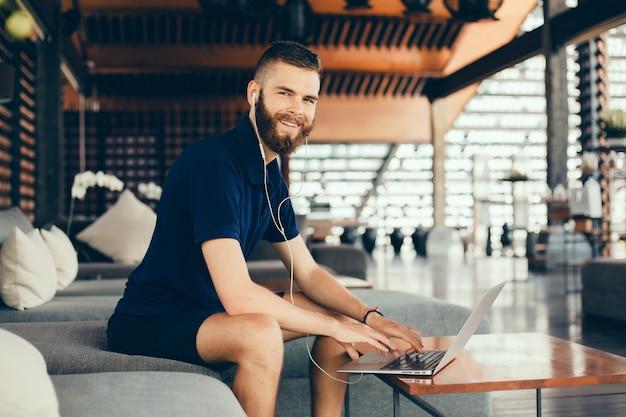 Jonge kerel met een baard werkt in een café, freelancer maakt gebruik van een laptop, doet een project Gratis Foto