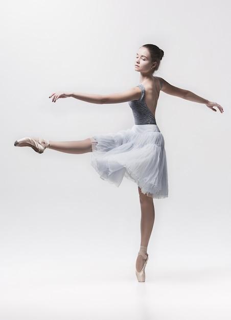Jonge klassieke danser die op wit danst Gratis Foto