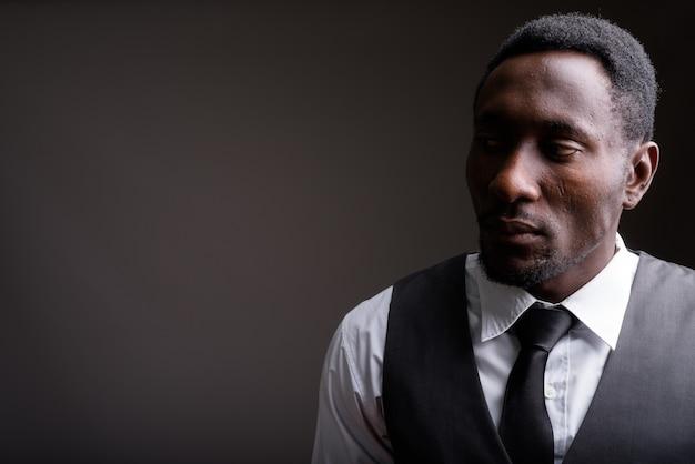 Jonge knappe afrikaanse zakenman tegen grijze achtergrond Premium Foto