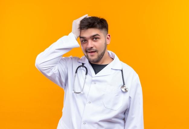 Jonge knappe arts die witte medische toga witte medische handschoenen en stethoscoop draagt zijn hoofd met hand die met vergeten gezicht kijkt dat zich over oranje muur bevindt Gratis Foto