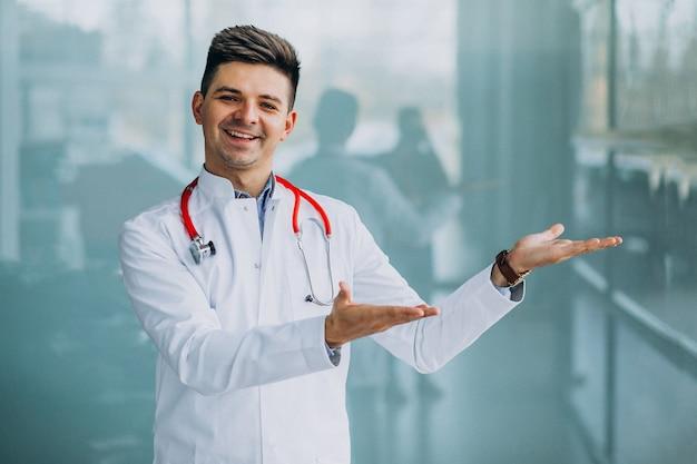 Jonge knappe arts in een medische robe met stethoscoop Gratis Foto