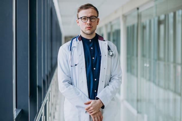 Jonge knappe arts met een stethoscoop bij kliniek Gratis Foto