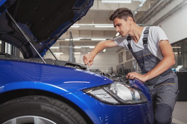 Jonge knappe autowerktuigkundige die voertuig in zijn garage herstelt Premium Foto