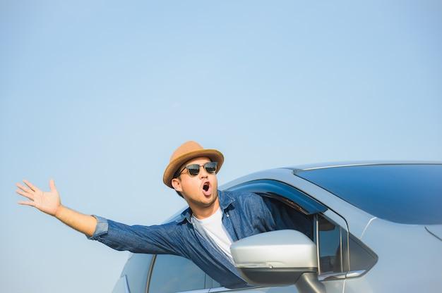 Jonge knappe aziatische mensen drijfauto om op zijn tijd van de vakantievakantie met mooie blauwe hemel te reizen. Premium Foto
