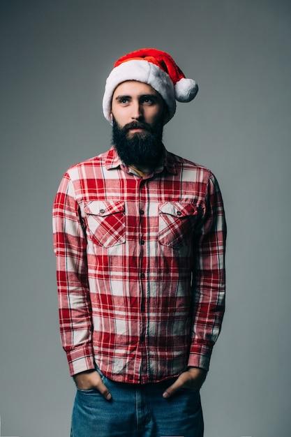 Jonge knappe bebaarde man met rode kerstmuts op grijze muur Gratis Foto