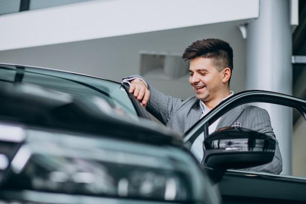 Jonge knappe bedrijfsmens die een auto in een autotoonzaal kiest Gratis Foto