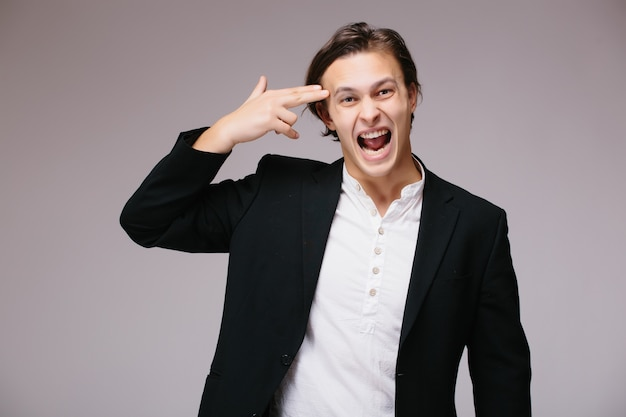 Jonge knappe bedrijfsmens die kostuum en stropdas over geïsoleerde muur draagt, schiet en doodt zichzelf wijzende hand en vingers als een pistool Gratis Foto