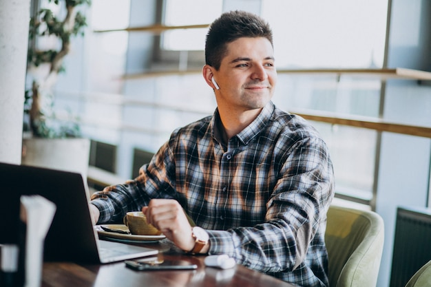 Jonge knappe bedrijfsmens die laptop in een koffie met behulp van Gratis Foto