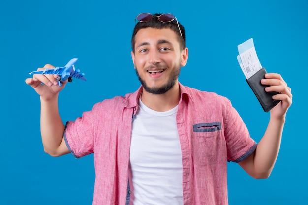 Jonge knappe de holdingsstuk speelgoed van de reizigerskerel vliegtuig en luchtkaartjes die camera bekijken die vrolijk met gelukkig gezicht glimlachen die zich over blauwe achtergrond bevinden Gratis Foto
