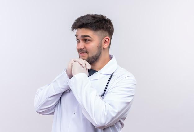 Jonge knappe dokter, gekleed in witte medische jurk witte medische handschoenen en een stethoscoop kijken naast gefascineerd staande over witte muur Gratis Foto