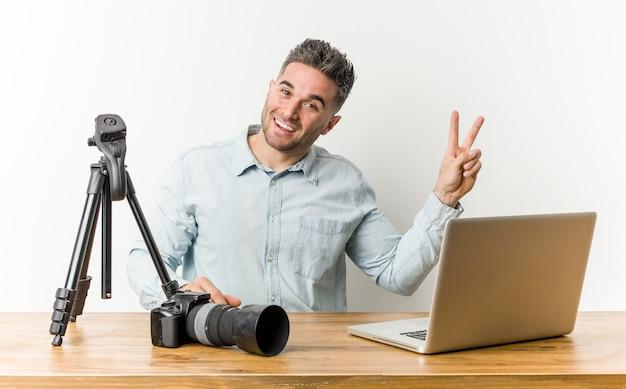 Jonge knappe fotografieleraar vrolijk en zorgeloos met een vredessymbool met vingers. Premium Foto