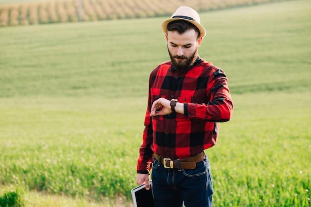 Jonge knappe gebaarde landbouwer met tablet die zich op tarwegebied bevindt en op de klok kijkt Premium Foto