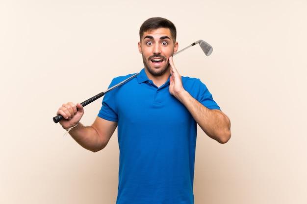 Jonge knappe golfspelermens over geïsoleerde muur met verrassing en geschokte gelaatsuitdrukking Premium Foto