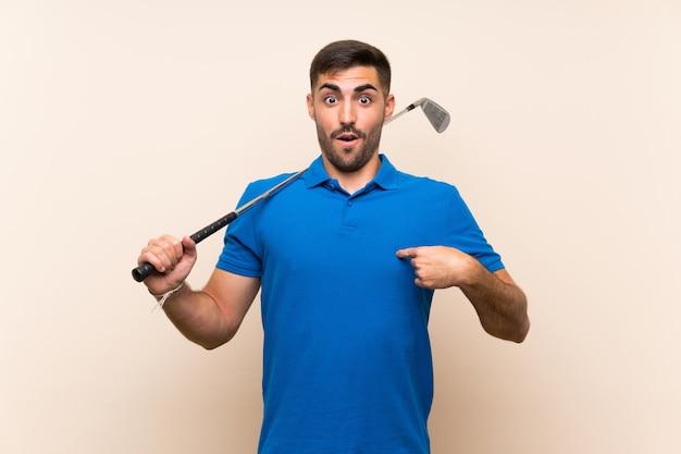 Jonge knappe golfspelermens over geïsoleerde muur met verrassingsgelaatsuitdrukking Premium Foto
