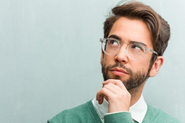 Jonge knappe het gezichtsclose-up die van de ondernemersmens denken en omhoog kijken, verward over identiteitskaart Premium Foto
